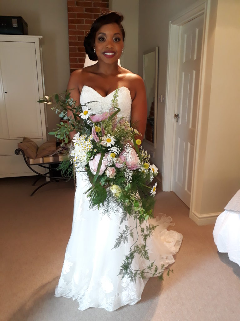 Cascading handtie bouquet with lots of peonies, roses and daisies for the beautiful bride