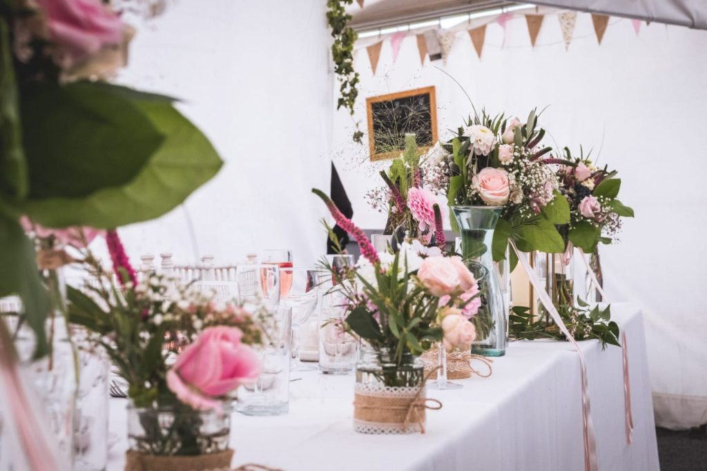 Bridesmaids' bouquets complementing the jars and bottles along the top table