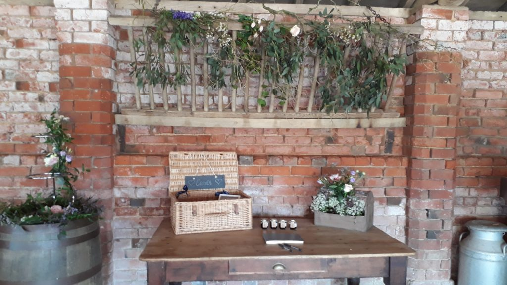 Contorted willow and eucalyptus with flowers in a loose swag above the cards table with the cake barrel ready for the American pies
