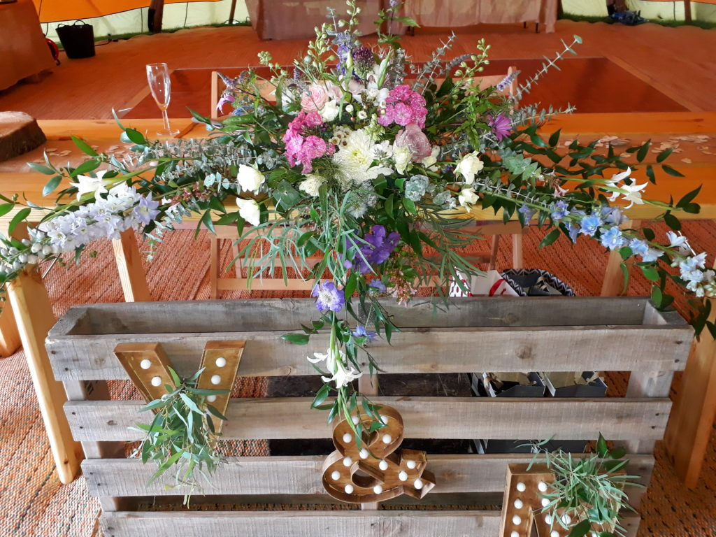 Wildflower style flowers above the lit initials made by the talented Groom