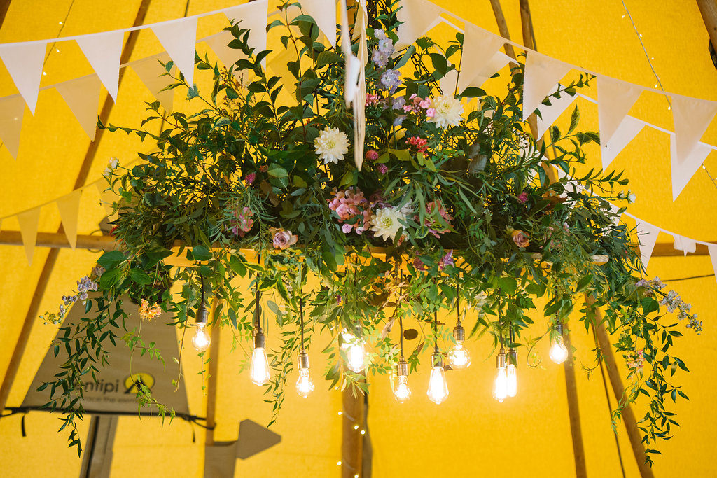 Hanging flowers on cherry wood board with edison bulbs. Photo: Light and Lace.  Tipi wedding