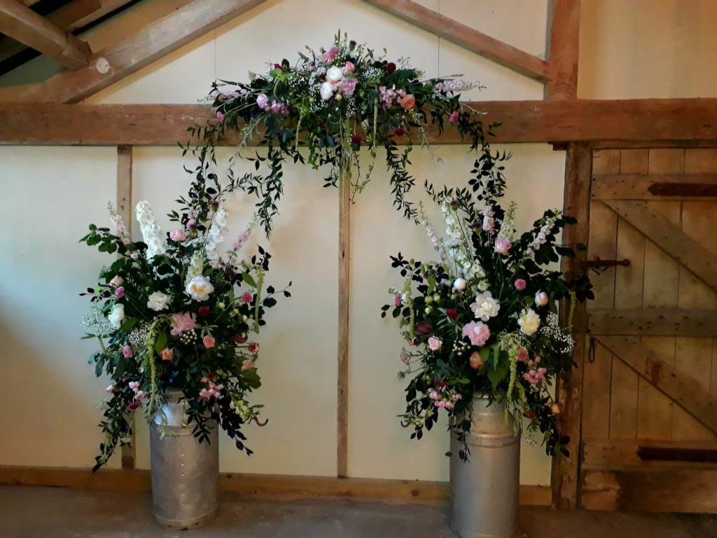 Stunning Peonies in milk churns creating an arch effect for a wedding blessing. June, Park Farm