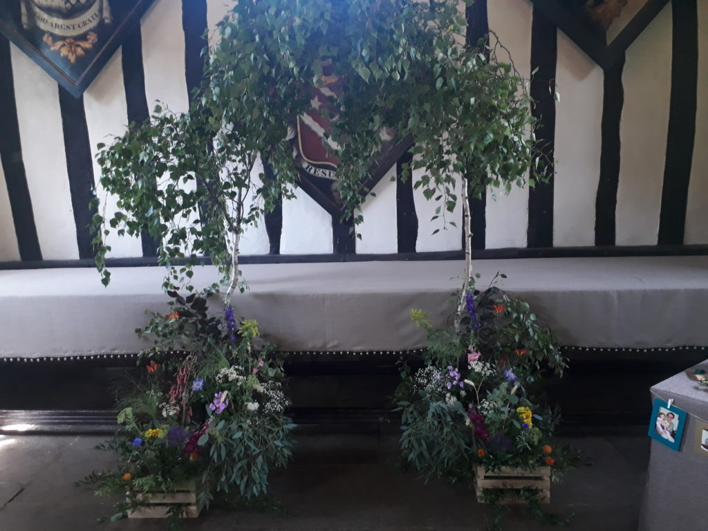 Delightful naturally leafy, colourful wild flower arch created in atmospheric Selly Manor
