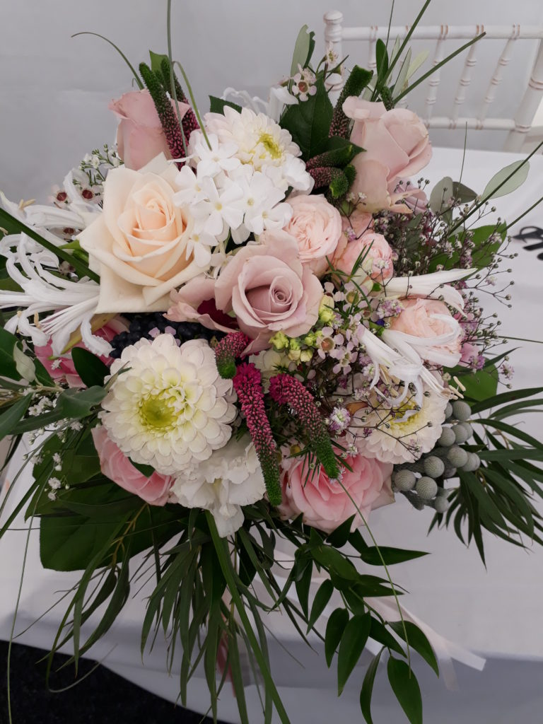 Silvery Brunia with seasonal Nerines and Dahlias with pastel and vintage shades.