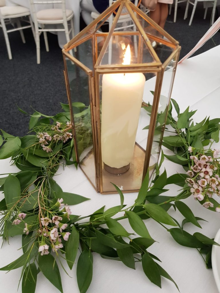 Simple foliage wax flower rings round these lovely lanterns for the tables