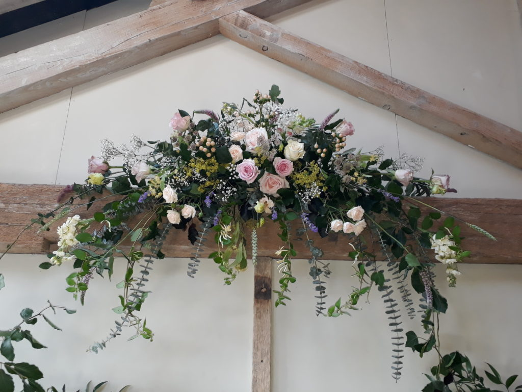 Lovely pastel roses and greenery beam arrangement for a farm barn wedding ceremony.