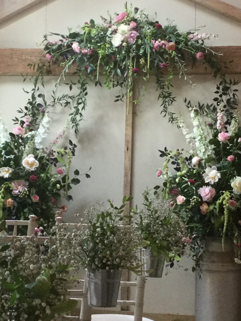 Ceremony Area framed with lovely flowers and foliage including Peonies and Roses