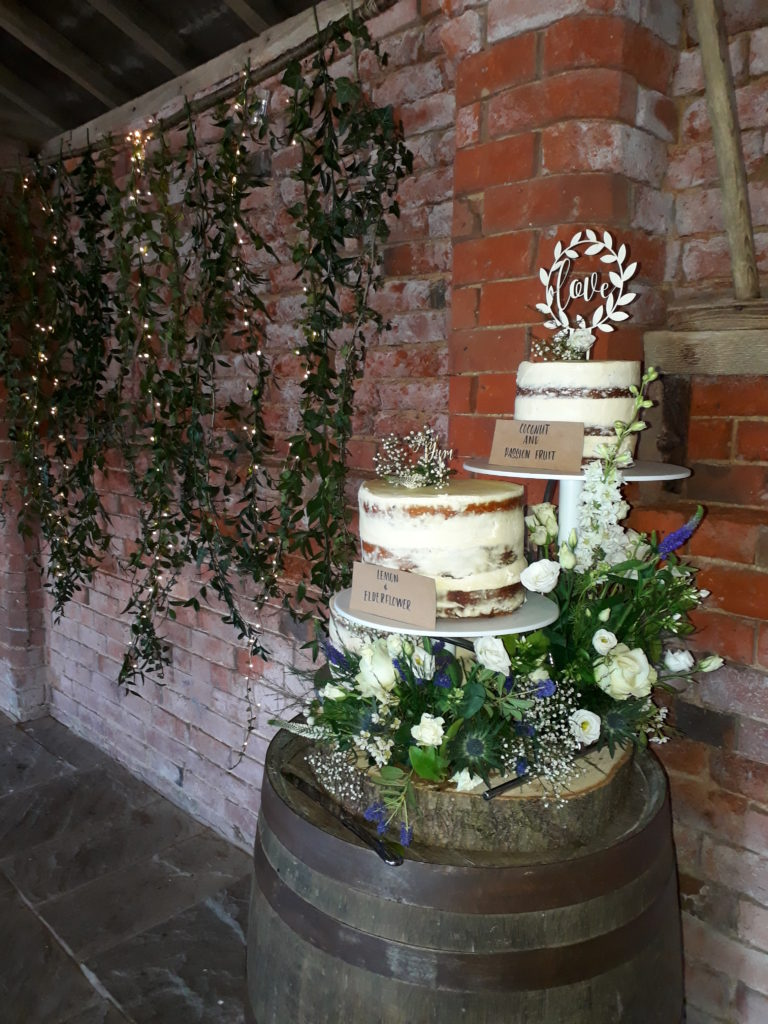 Greenery wall backdrop and cake at Park Farm.