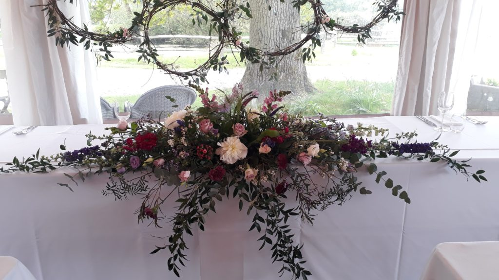 Cascading long and low top table centre and grapevine hoops behind