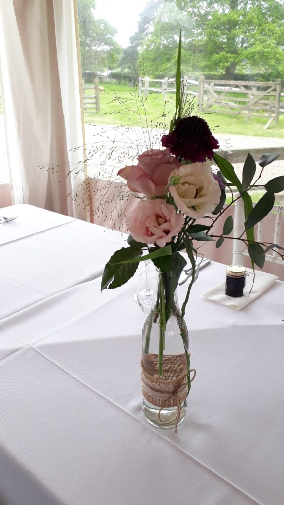 Alterating bottles and jars down the trestles creating pretty effect but still allowing plenty of space for food platters