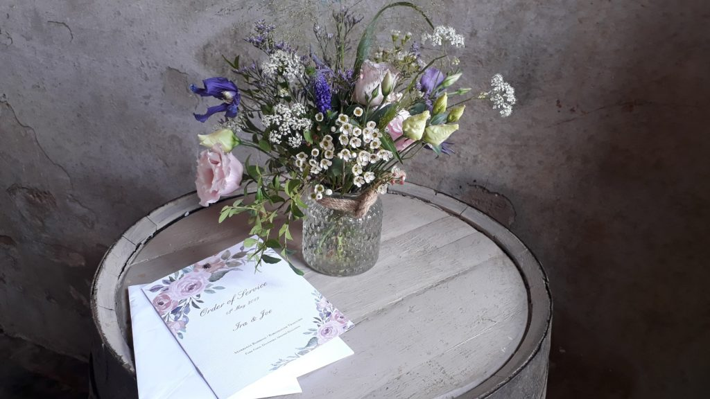 Relaxed natural jars of flowers on the Lambing Shed barrels