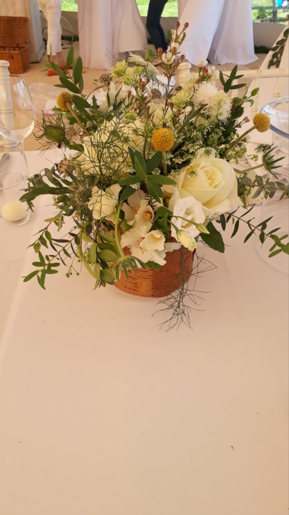 Garden flowers and herbs in the bark and wood containers