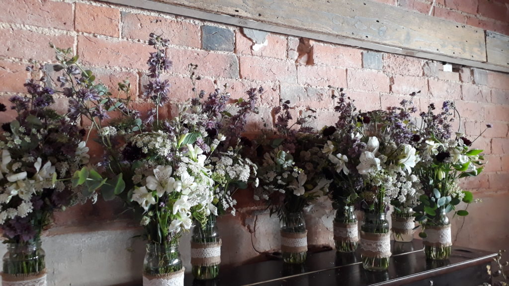 Groom's mum made a fab job with the table jars - here the first ones of the trios being lined up and then beautiful roses added in other jars