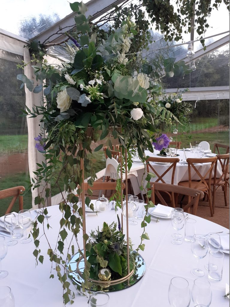Tall table centres on a mirror reflect like the lake and a lower placement with a woodland vibe