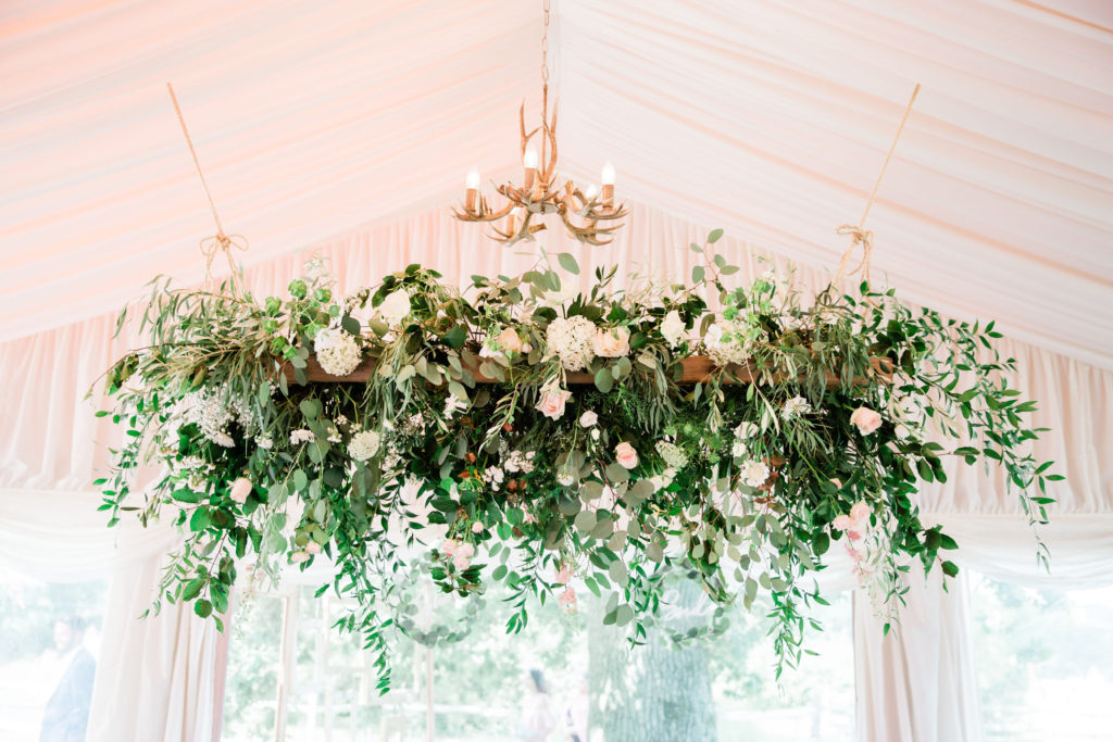 Cascading greenery and soft pastel flowers on a hanging vintage ladder Photo: Sophie Evans