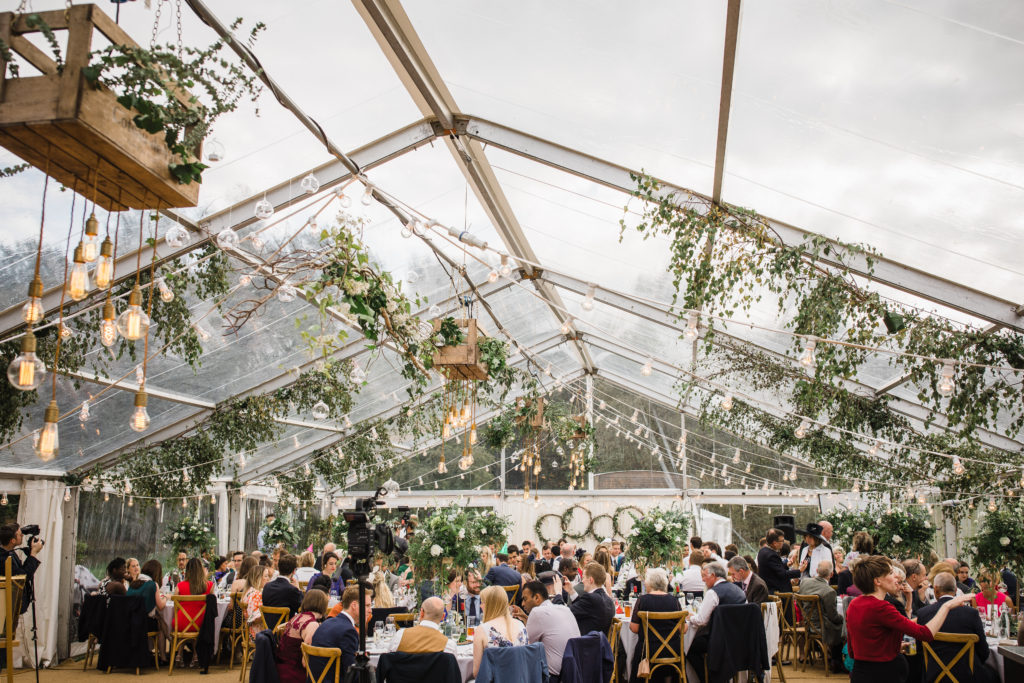 Belvoir castle, Frog Hollow: Clear marquee in magical lakeside/woodland setting decked with leafy branches and flowers.  Photo: Matt Brown Photography